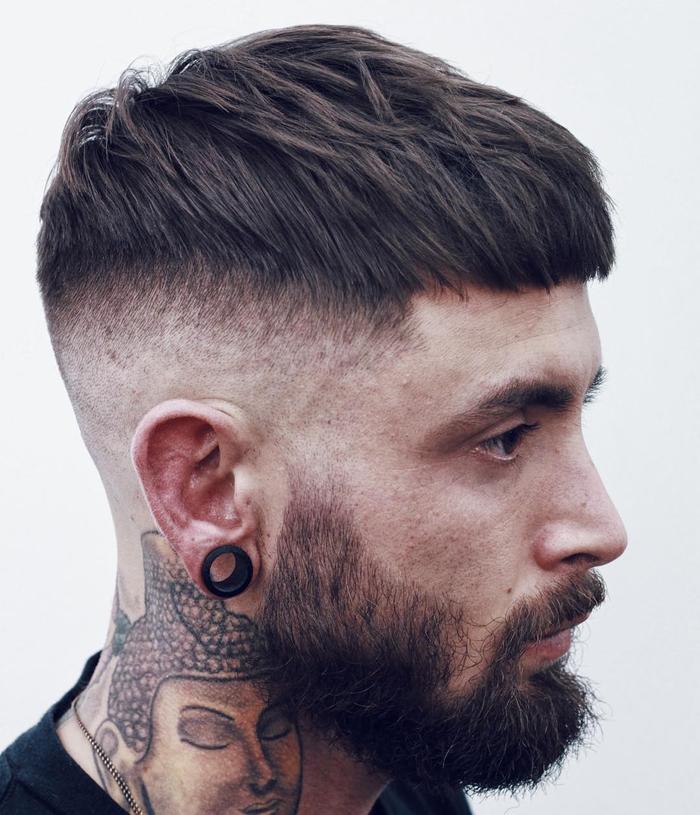 une coupe homme rasé coté avec dégradé haut à blanc et barbé déconnectée pour un look hipster