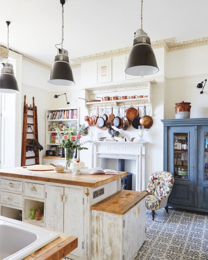 exemple de cuisine rustique blanche, avec vaisselle, casseroles suspendues, cheminée blanche, ilot central blanc patiné, carrelage blanc et gris à motifs floraux, suspensions gris foncé, vaisselier bleu