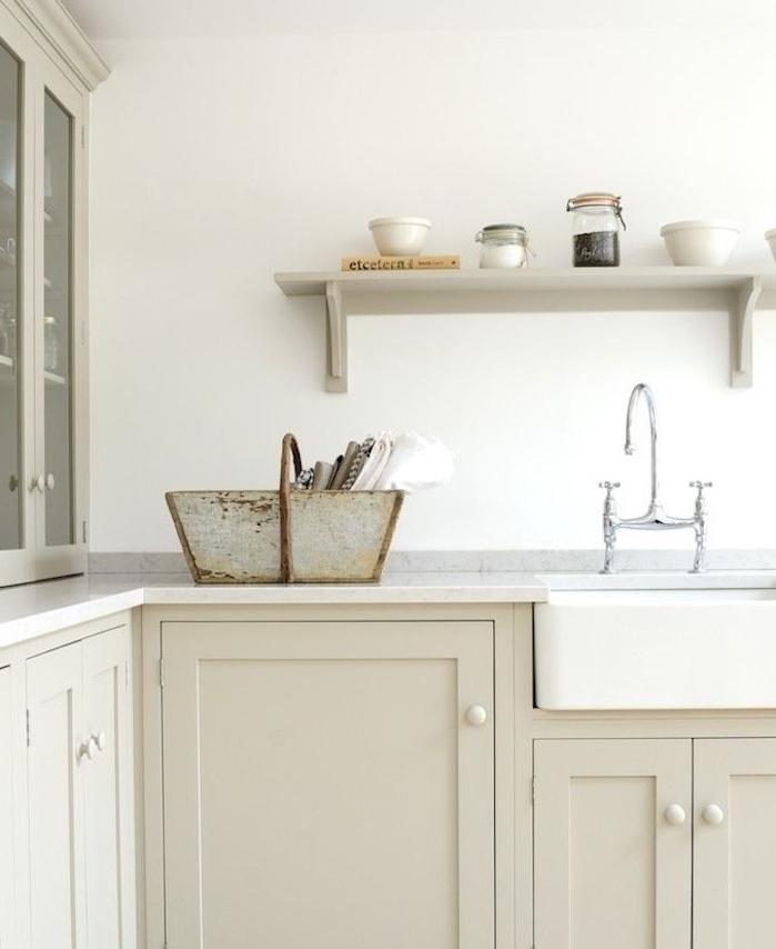 façade cuisine couleur taupe claire avec plan de travail blanc et étagère gris perle, robinetterie grise, vasque à poser blanche, panier en métal rangement vaisselle