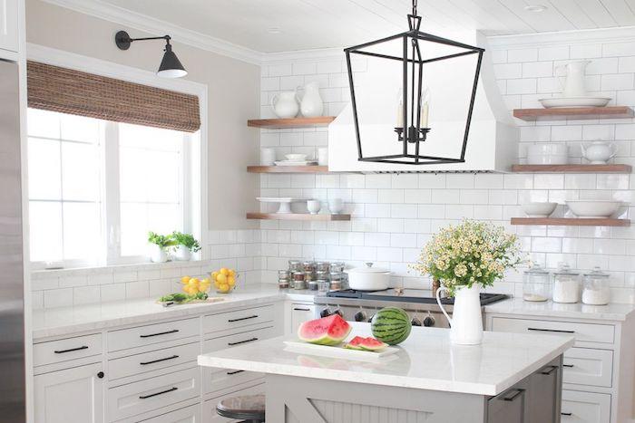 exemple de cuisine rénovée en blanc avec credence carrelage blanc, etageres en bois surchargées de vaisselle blanche, ilot central gris avec plan de travail blanc, suspension noire