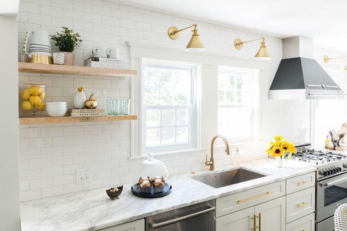 cuisine rénovée blanche avec electromenager inox, plan de travail marbre, credence carrelage blanc, etageres en bois, aspirateur gris, poignées, lampes et robinetterie dorée