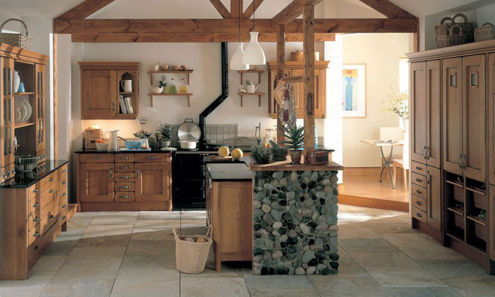 cuisine rustique en bois avec poutres apparente, ilot central bois décoré de pierres, dallage en pierre, vaisselier et meuble cuisine bois