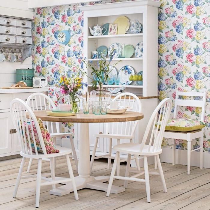 modele de cuisine campagnarde, style shabby chic avec mur habillé de papier peint à imprimé floral, table et chaises coin repas en bois, facade cuisine blanc et vaisselier blanc, décorée de vaisselle fleurie