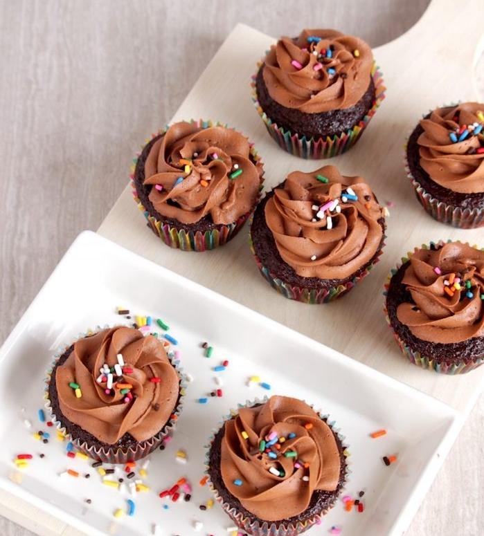 cupcakes au chocolat avec glacage au chocolat et beurre et deçoration de vermicelles colorées dessus