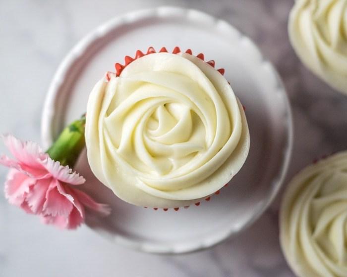 recette de glacage au fromage à la crème sur un cupcake, façon fleur, décoration de fleur à côté