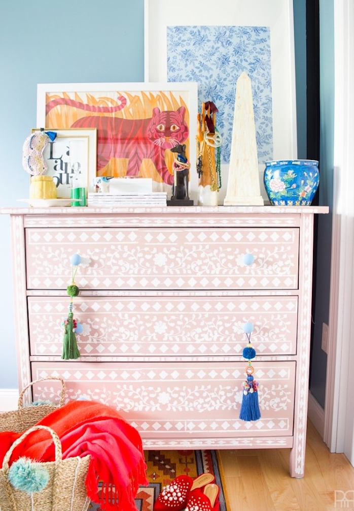 customiser meuble ancien, commode relookée au pochoir, motifs floraux blancs sur une peinture de fond rose, objets decoratifs orientaux