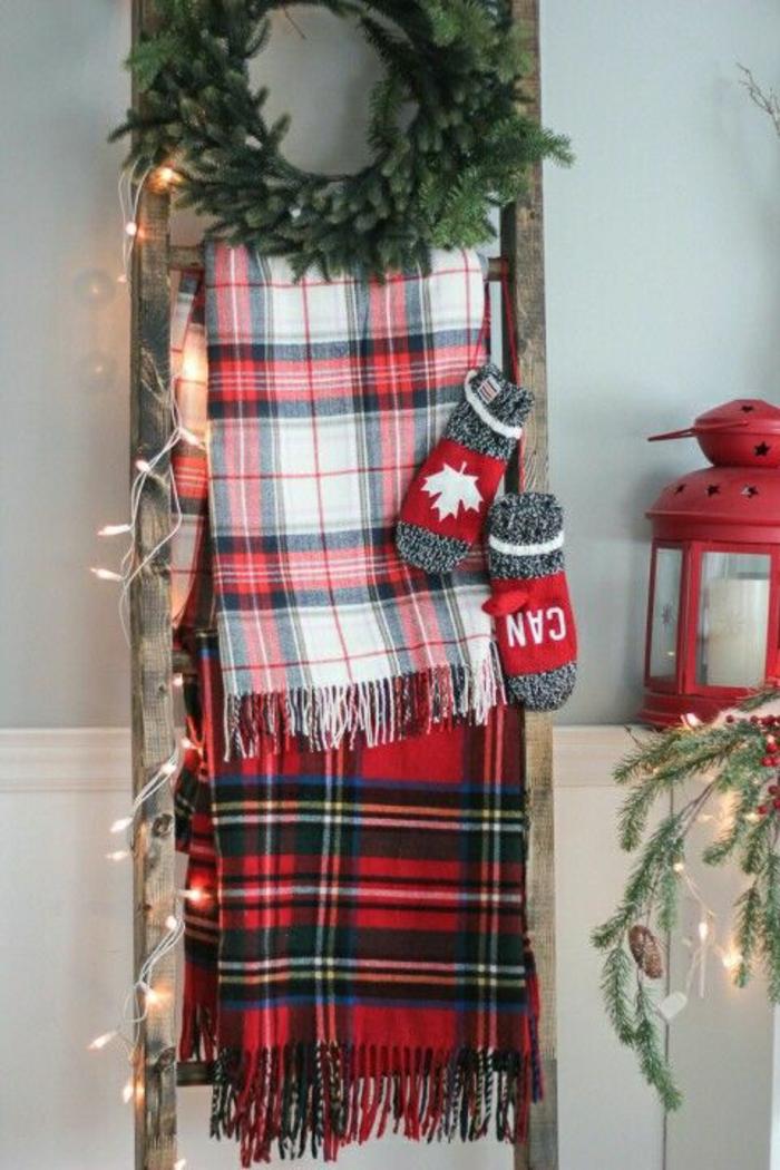 bricolage de noel, déco de noël à faire soi même facile, avec une échelle, appuyée contre le mur, deux écharpes à carreaux rouges, noires et blancs, couronne faite de feuilles vertes de sapin, deux gants en gris et rouge, petit luminaire en rouge, échelle ornée avec des guirlandes lumineuses
