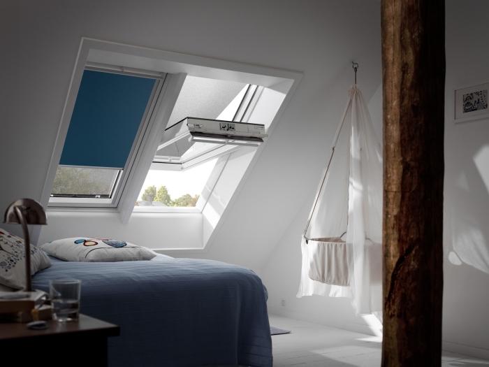 comble aménagé, pièce à coucher au grenier avec meubles en bois et murs blancs, couverture de lit bleu foncé et coussins blancs