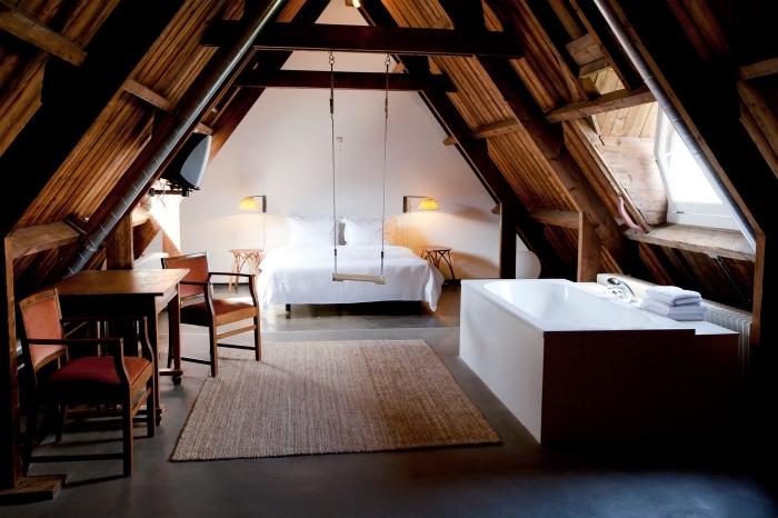 comble aménagé, pièce sous combles aux murs blancs et plancher noir, meubles de chambre à coucher en bois ancien