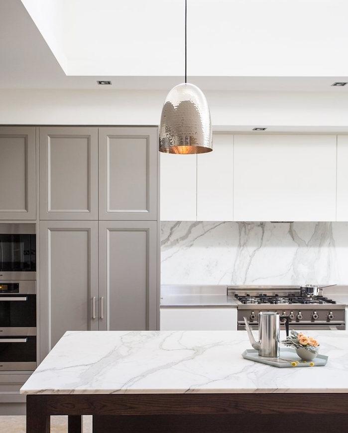 façade cuisine couleur grege, plan de travail ilot central et crédence marbre, suspension grise, meuble haut et bas blanc