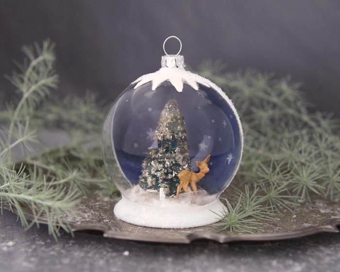 une decoration de noel fait main qui représente une boule de neige semi-transparente à peinture effet neige, avec des figurines de noël à l intérieur du globe