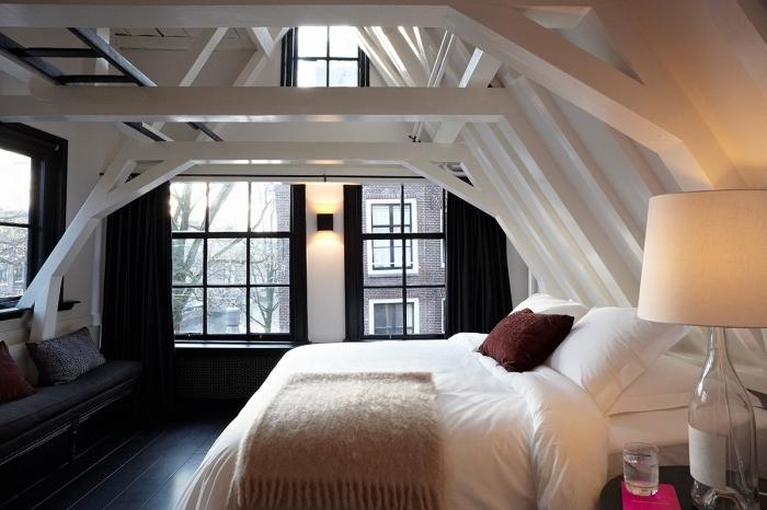 decoration chambre mansardée adulte, pièce en blanc et noir avec plancher en bois foncé et plafond en bois peint blanc