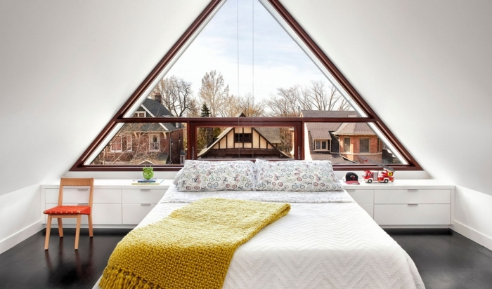 chambre à coucher au grenier décorée simple et moderne avec grand lit et meubles en bois peints en blanc