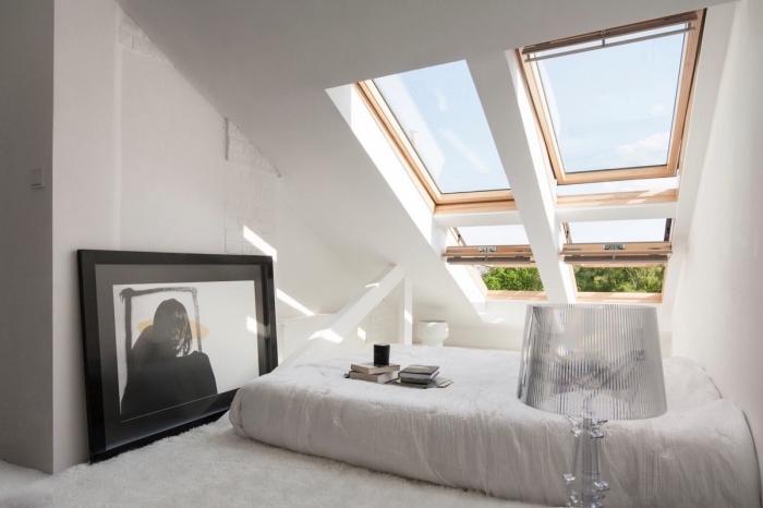 comble aménagé, chambre à coucher blanche aux murs blancs avec lit bas et fenêtre de plafond en bois clair