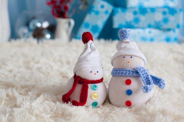 comment faire un bonhomme, décoration de Noël avec tapis blanc moelleux et boîtes de cadeaux bleues à flocons de neige