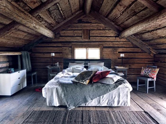 chambre mansardée, chambre à coucher au plafond et murs en bois massif, tête de lit en palette peinte en bleu foncé