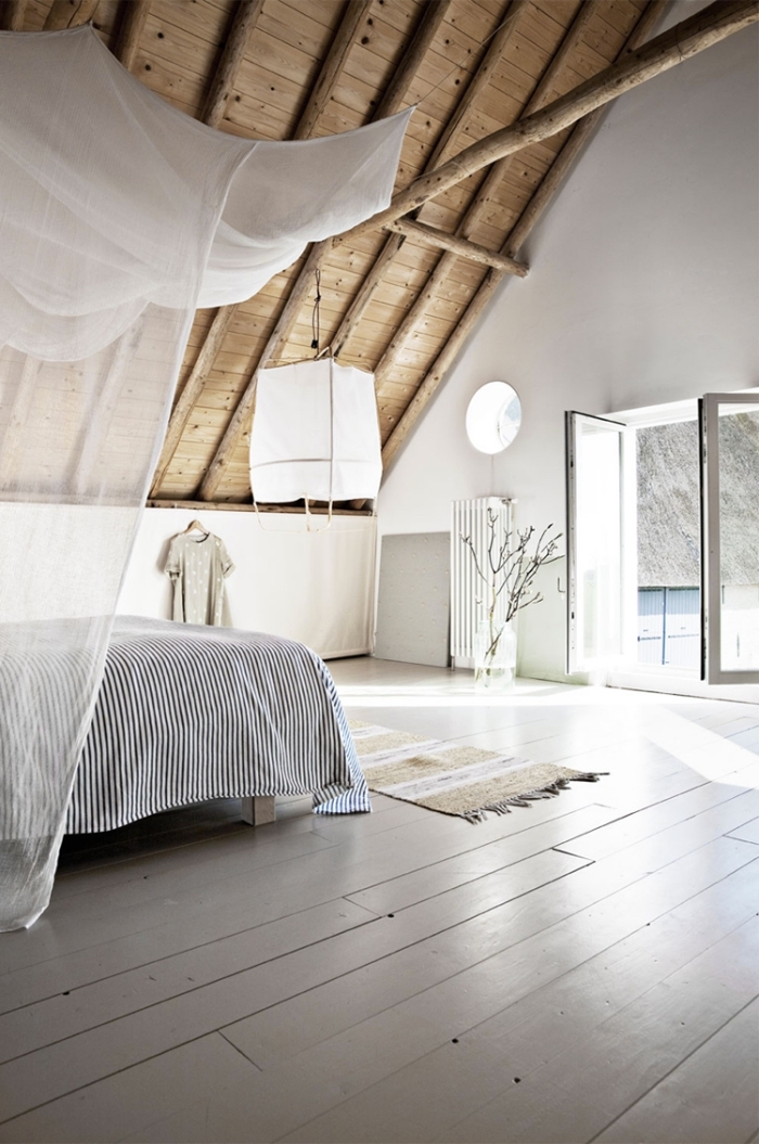 amenagement combles, chambre à coucher aux murs blancs avec plafond de bois clair et poutres de bois décoratives