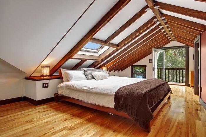 décoration moderne de la chambre à coucher au grenier avec murs blancs et poutres en bois marron foncé