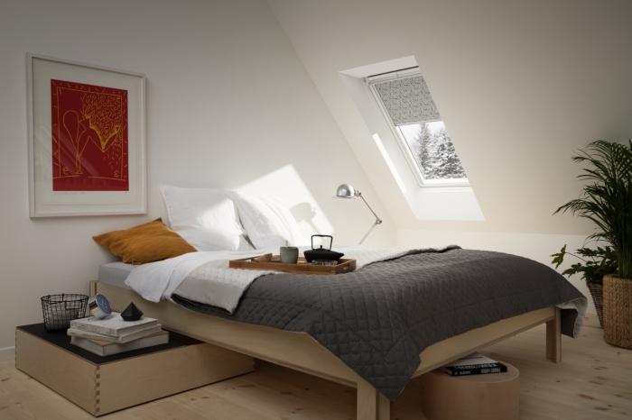 chambre mansardée aux murs blancs avec petite fenêtres de plafond et plancher en bois stratifié clair