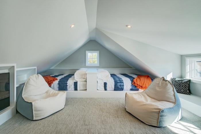 amenagement grenier aux murs peints en bleu clair et grand tapis en beige, déco simple avec poufs en blanc et bleu clair