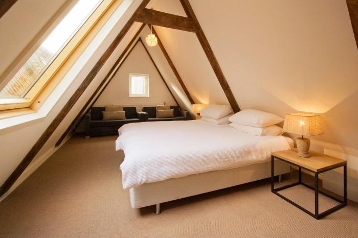 comble aménagé, déco simple de chambre parentale au grenier avec tapis beige et charpente en bois foncé