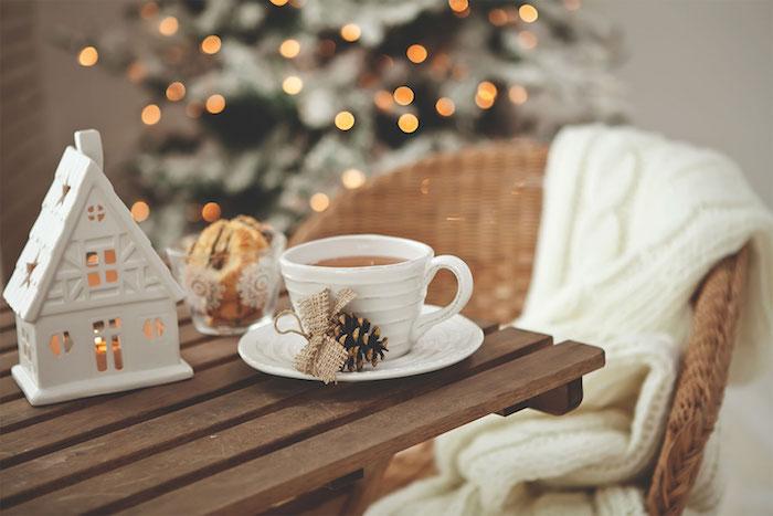 deco cocooning hiver, photophore figurine maisonnette blanche, table en bois, tasse de café avec pomme de pin, chaise en rotin avec plaid, sapin de noel sur le fond