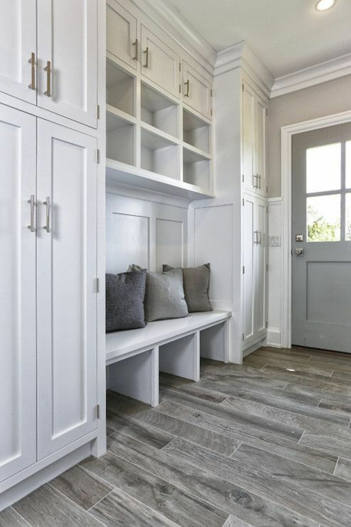 decoration couloir gris et blanc, banc blanc avec trois coussins en gris anthracite, gris clair et blanc, étagères blanches, sol recouvert en parquet PVC en gris clair et foncé, porte en gris perle