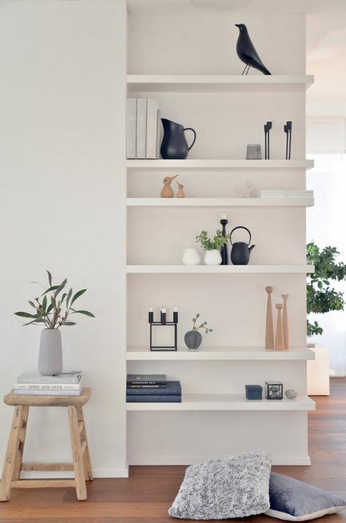 deco couloir avec des étagères blanches et des objets déco en céramique noire et en bois clair, bougeoir noir avec trois bougies blanches, tabouret bas en bois clair, vase blanc avec des feuilles vertes de plante, deux coussins en gris clair et en gris anthracite, corbeau en céramique noire