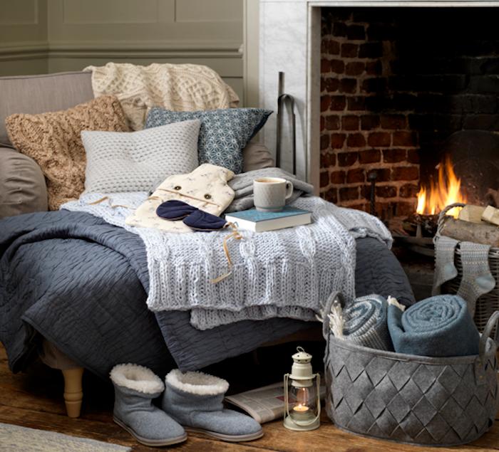 deco d hiver cosy, textiles, couvertures jetés, plaids et coussins sur un canapé gris cosy, pantoufles hiver, panier rangement de textiles, parquet bois brut