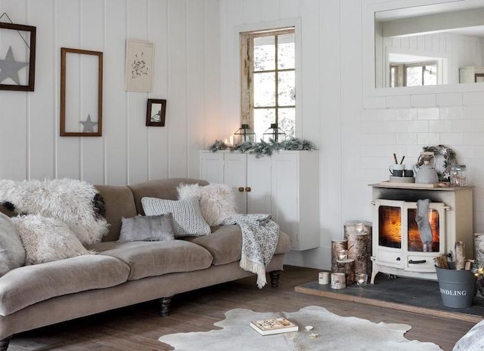 idee dco cocooning salon hygge, canapé gris, cheminée rustique, teintes neutres, parquet bois brut, lambris blanc, peau animale, deco vintage buches de bois
