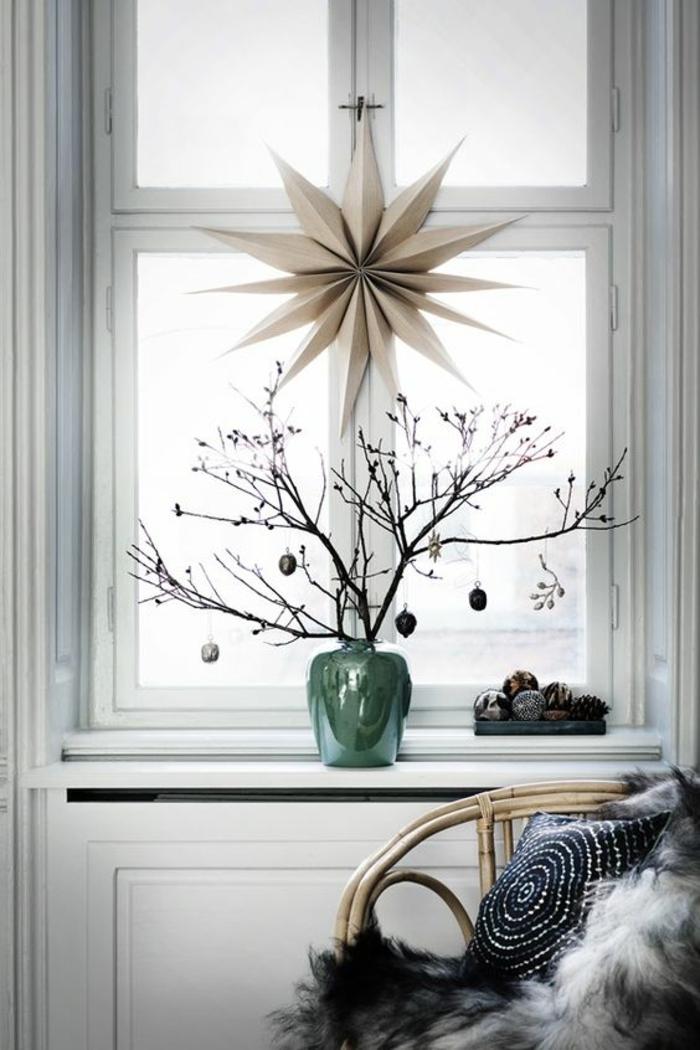 bricolage de noel avec une étoile en papier pour suspendre sur la fenêtre, ou pour mettre au sommet du sapin, branches d'arbre décorées avec des petites boules de noel et mises dans un vase vert brillant