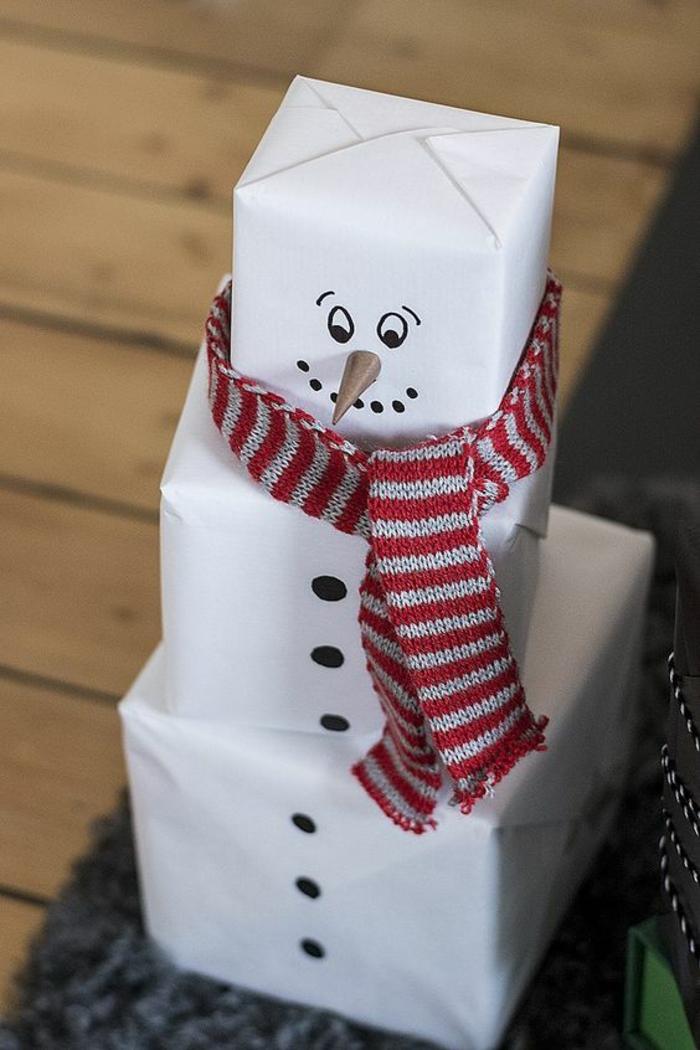 bricolage de noel bonhomme de neige fait avec trois paquets blancs et une écharpe en coton, a rayures horizontales rouges et blanches, idée originale pour empaqueter les cadeaux de la famille