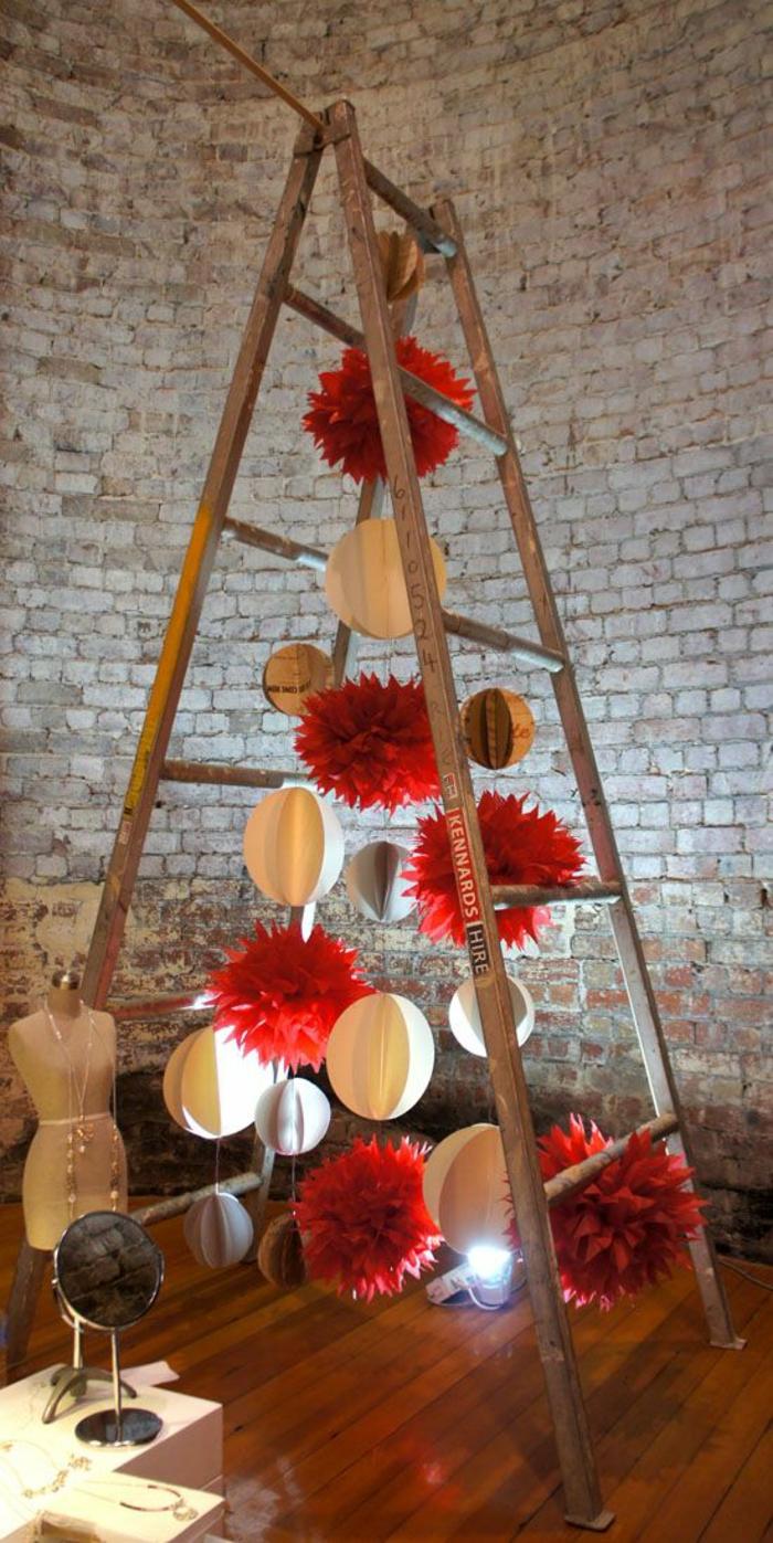 bricolage de noel avec une échelle ouverte en bois gris et plein de grands pompons rouges en carton et des grandes boules en carton en couleur crème, illuminées avec un spot encastré dans le sol en parquet PVC