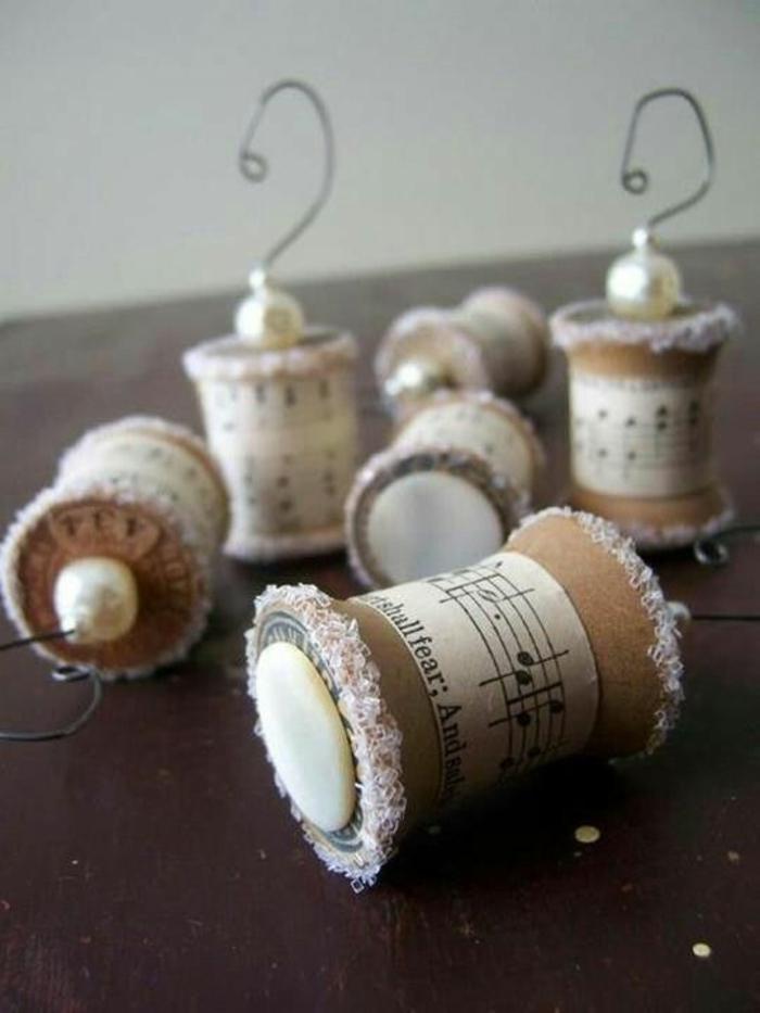 activite manuelle noel avec des bouchons en liège, décorés de parties de partitions musicales, dentelle blanche et des perles minuscules en verre en nuances rosées, du fil métallique pour faire les suspensions en forme de crochets