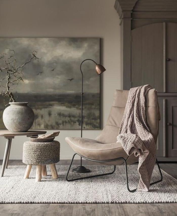 armoire et mur couleur taupe, chaise, tapis et couverture couleur taupe clair, table en bois et tabouret tricot
