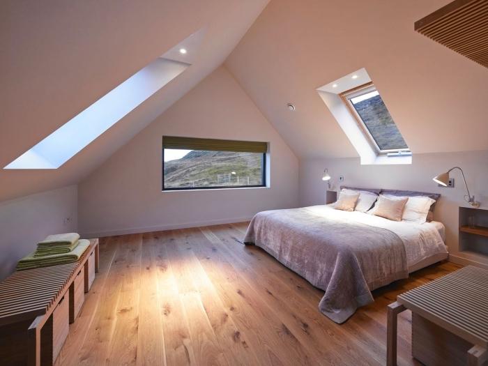aménagement au grenier simple et moderne avec meubles de bois et grand lit couvert de coussins et plaids