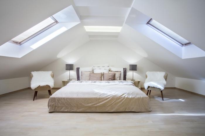 aménagement de combles, deco chambre parentale, pièce sous combles avec plancher en bois clair et fenêtres de toit, grand lit à la couverture beige et coussins marron