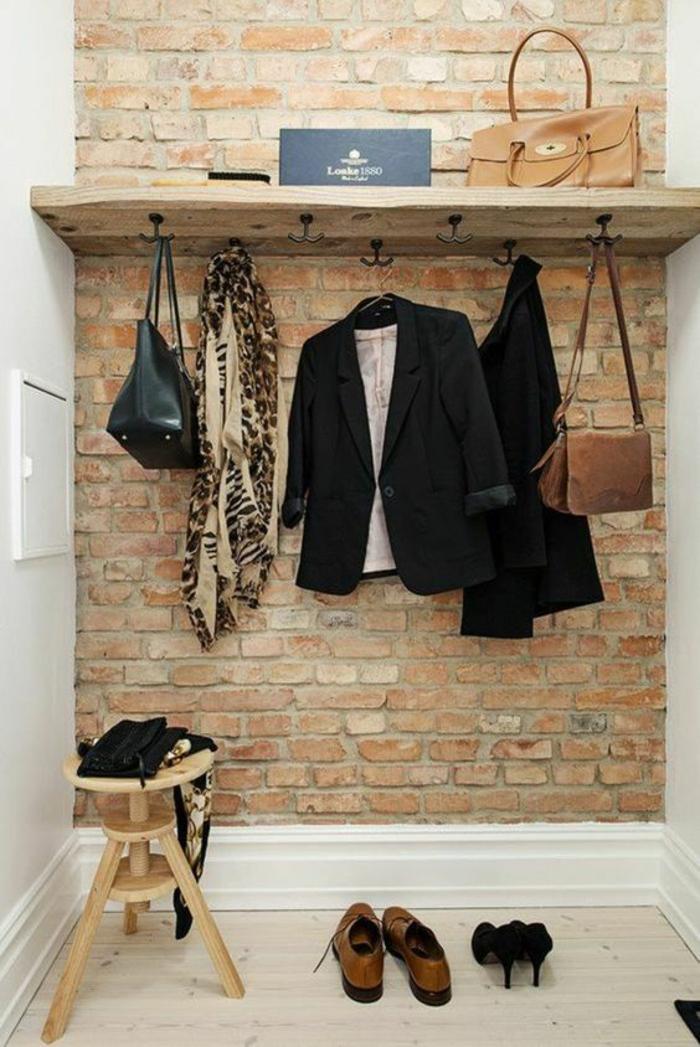 quelle couleur pour un couloir, mur en briques rouges, avec étagère en bois clair brut et des patères en métal noir, petit tabouret bas en bois clair, sol en parquet blanc effet bois peint
