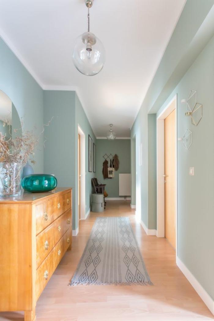 deco couloir en bleu pastel et blanc, avec tapis en gris clair et blanc, lampadaire en forme de boule en verre transparent, murs en bleu pastel, grand meuble en bois clair avec bol décoratif en verre vert émeraude