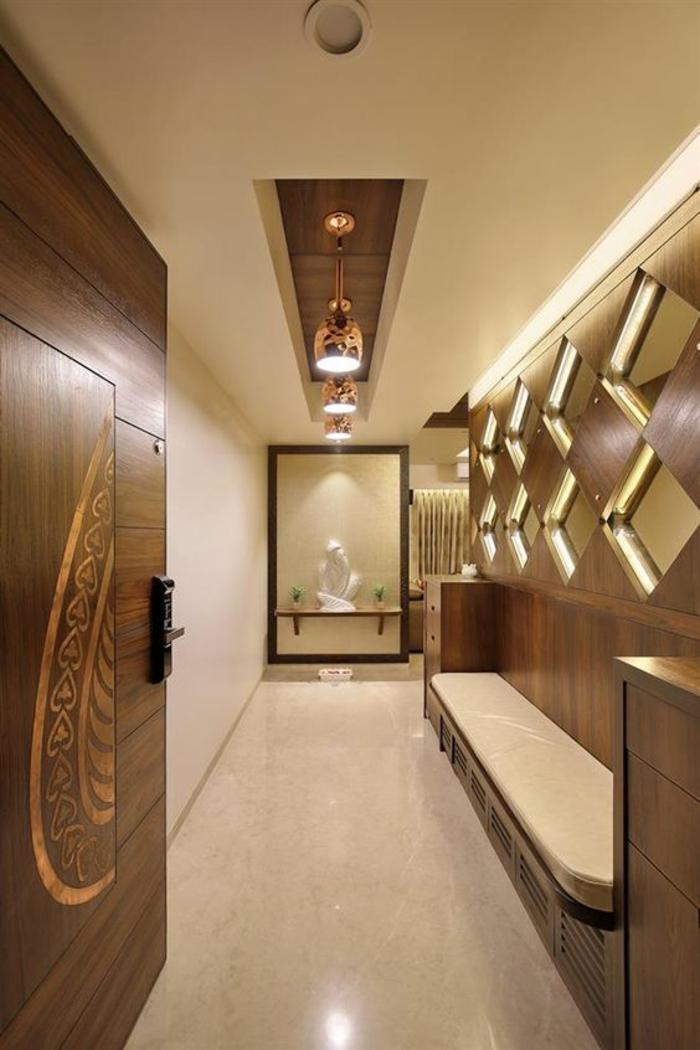 idée entrée en marron, porte massive avec motifs décoratifs floraux, banc avec coussin long en beige, huit miroirs en forme de losanges installés dans les niches du mur, trois lampadaires en matière imitation bronze brillant, installés dans une niche rectangulaire au plafond