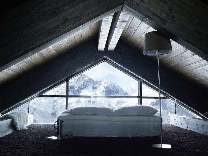 déco simple de la chambre à coucher au grenier avec grande fenêtre donnant sur les montagnes et plafond en bois