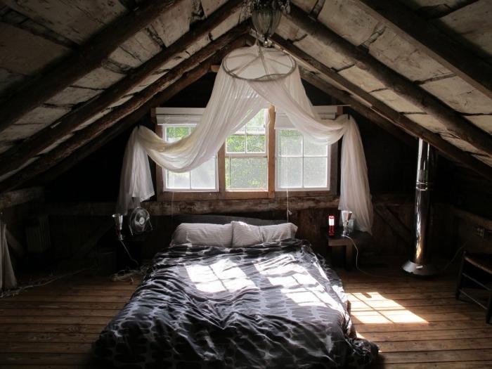 piece mansardée, modèle de lit bas avec décoration à baldaquin, aménagement de chambre en bois foncé