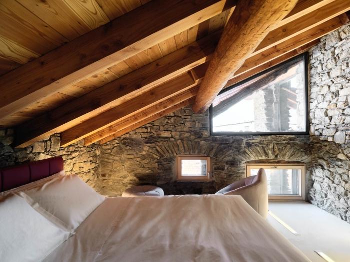 chambre à coucher de style rustique et campagne avec revêtement des murs en pierre et plafond avec poutres en bois