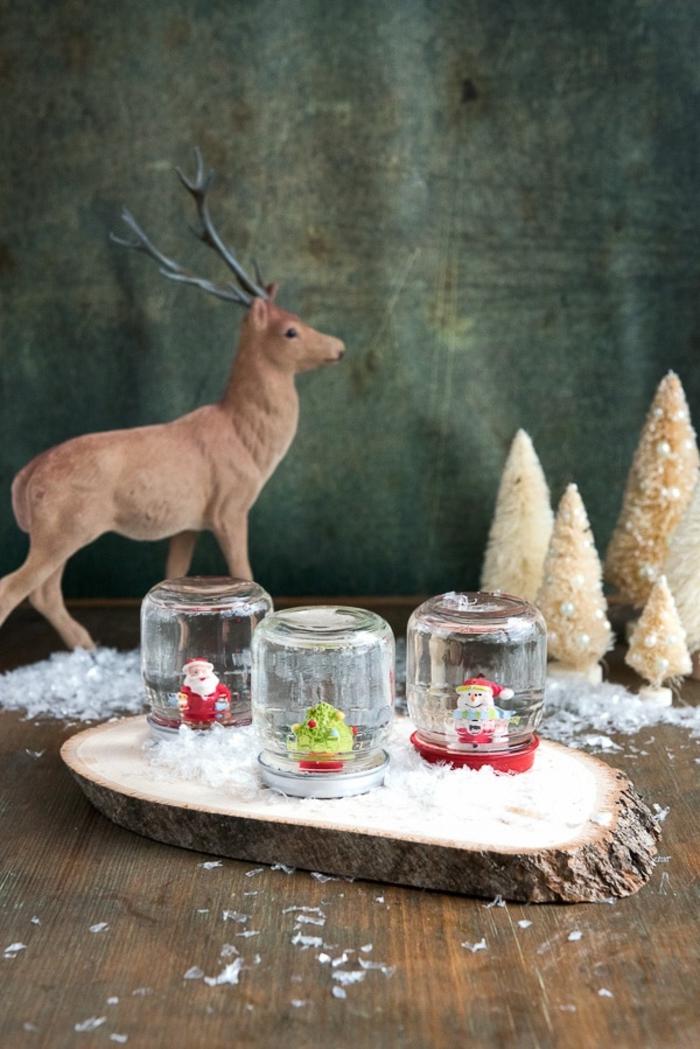 deco de noel fait main centre de table originale avec des bocaux en verre recyclés et un rondin de bois comme base