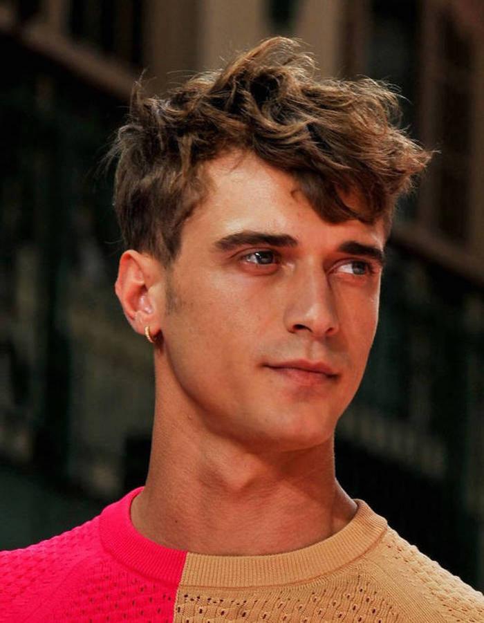 une coiffure hipster homme asymétrique avec mèche longue frisée qui retombe sur le visage