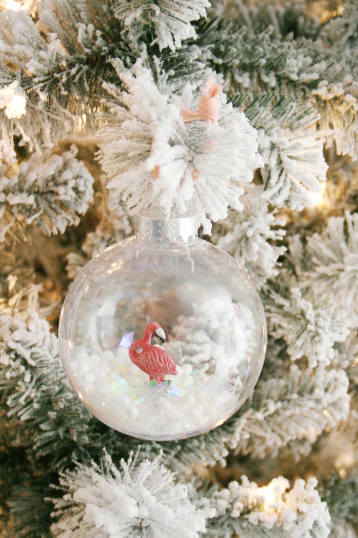 jolie idée pour une déco de noël à faire soi même facile à réaliser avec des boules de sapin transparentes, fausse neige et figurines flamant rose
