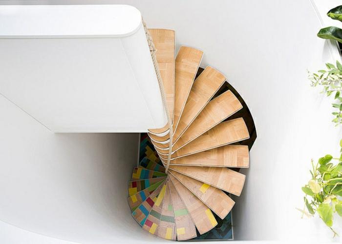escalier moderne avec des marches en beige couleur bois avec des petits éléments colorés en jaune, rouge et bleu turquoise, escalier bois en forme de spirale