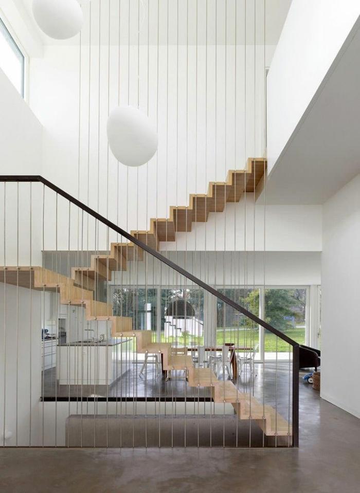 escalier moderne en forme de zig-zag, en couleur beige clair, garde corps en métal noir et des grandes boules blanches sur les murs