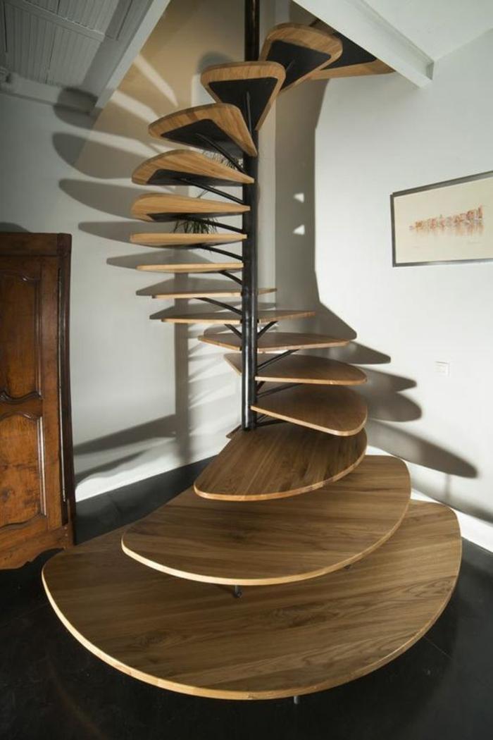 escalier design, escalier bois, escalier moderne, avec marches en forme de coquillages petits et grands qui se déploient dans la forme d'une spirale, carrelage en dalles noires, meuble armoire en marron foncé, murs blancs avec un grand tableau rectangulaire en cadre noir
