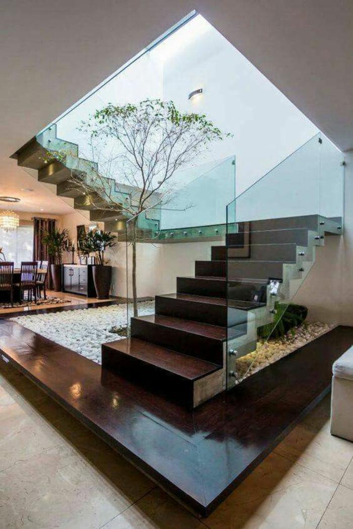 escalier bois laqué, avec garde corps escalier interieur en verre transparent, petit jardin japonais à la base de l'escalier, avec un arbre planté sur un sol recouvert de cailloux blancs décoratifs, carrelage aux dalles en couleur ivoire